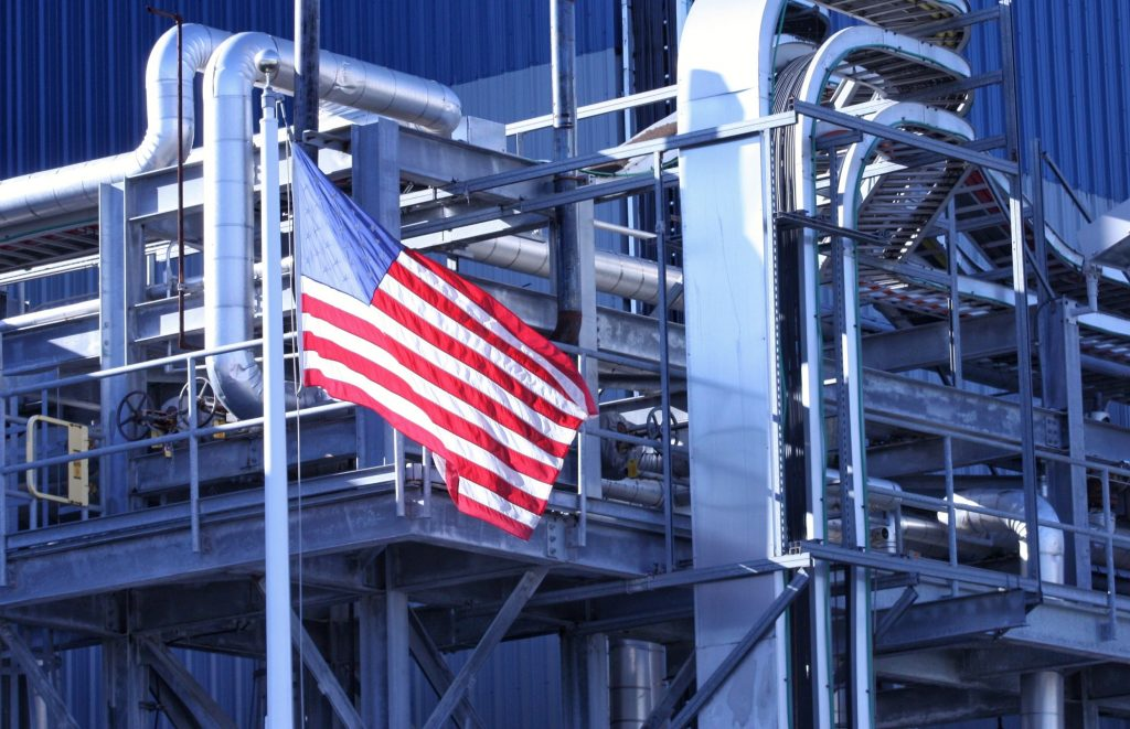 American flag flying outside a manufacturing facility supported by grants from Made in America Executive order