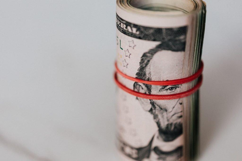 rubber banded bills signifying secured revenue for manufacturers